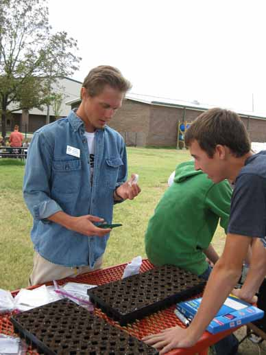 Ryan Norman of Delta Garden Study works with a high school student volunteer to prepare seeding trays.