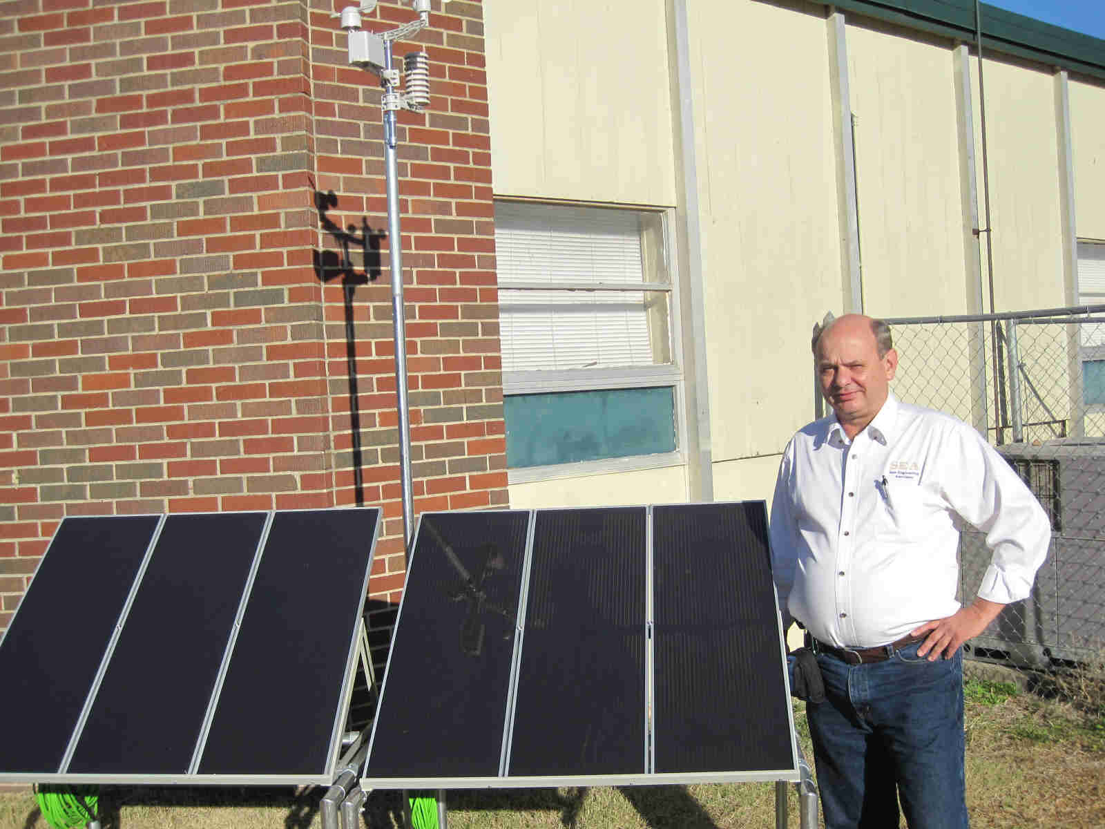 Dr. Bob stands by the assembled solar panel array with weather station installed.