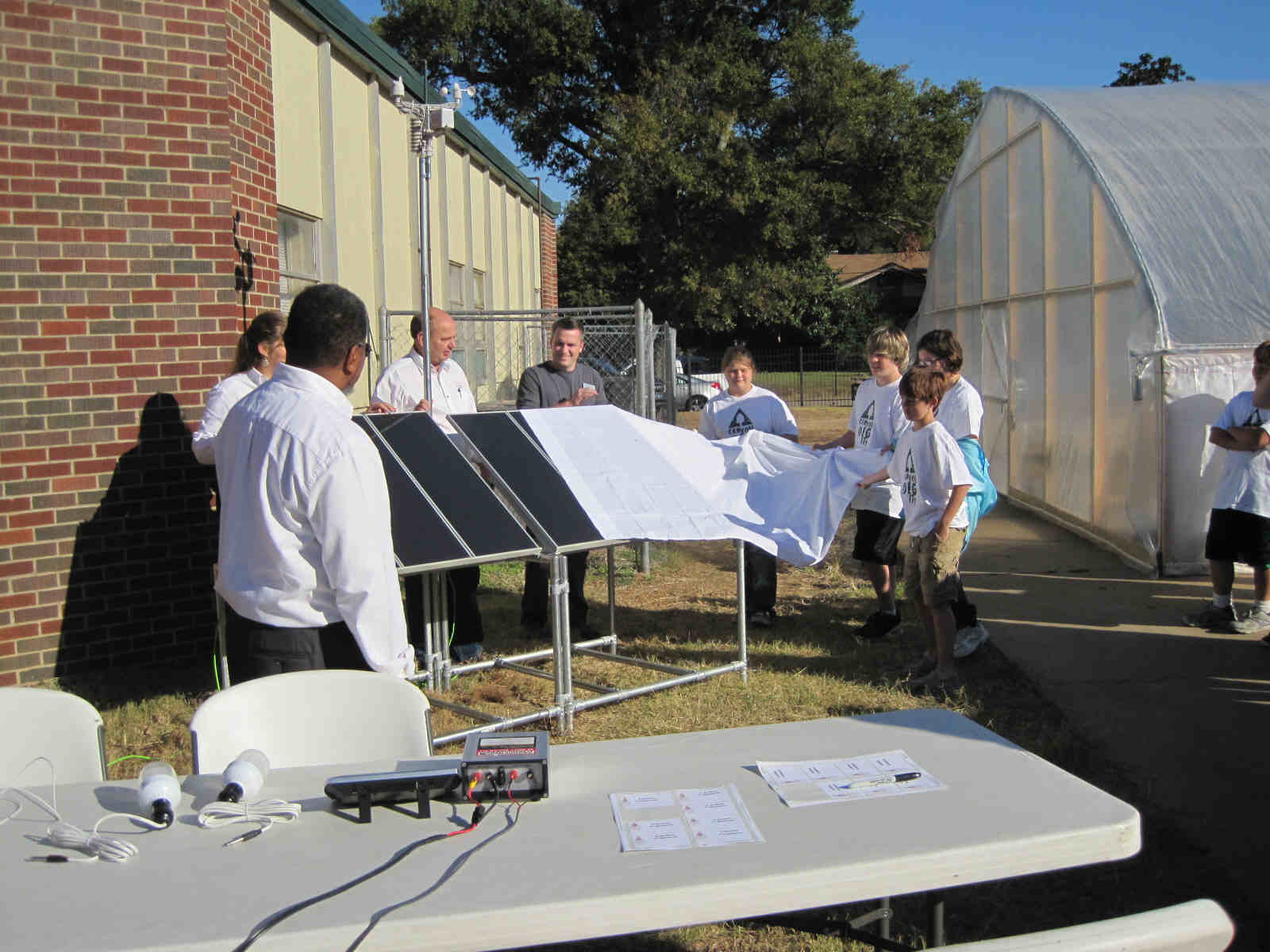 Students and faculity unveil their new solar array while members of MAREH assist.